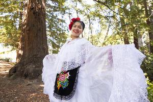 Graciela Ruiz in folklórico dress standing in front of redwood tree