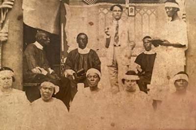 Sepia photo (approximately 1920s) showing a preacher and deacons on a platform with a young woman standing to their right with an open book in her hand. Church members / choir members are in the foreground.